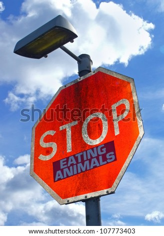 Large red road sign with the words Stop Eating Animals. - stock photo
