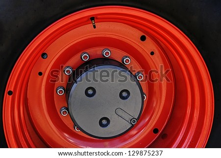 Large red wheel rim, for machinery used in agriculture. Detail - stock photo