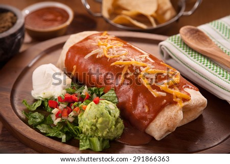 Large restaurant style burrito mexican food dinner with sides of guacamole chips - stock photo