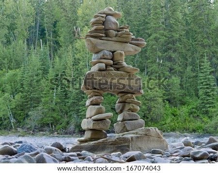 Large rocks stacked and balanced to form an Inuksuk stone landmark or cairn as a marker or monument in front of boreal forest taiga wilderness terrain - stock photo