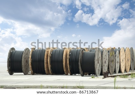 Large rolls of black cables on blue sky background - stock photo