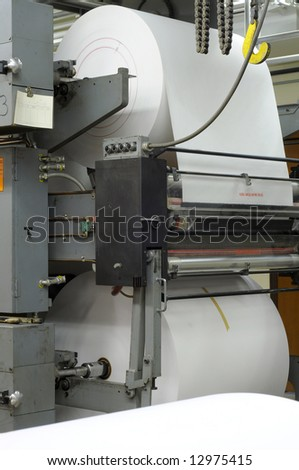 Large rolls of new paper on a four-web printing press - stock photo