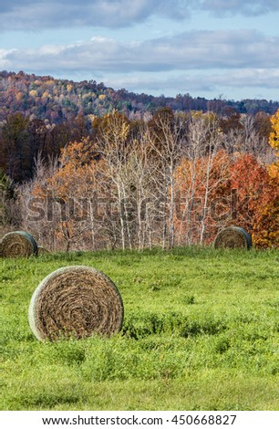 Large Round Hay Bales in Field with Autumn Colored Hills - stock photo