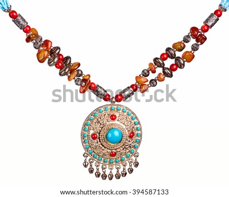 large round silver pendant with a large turquoise stone in the middle of a chain with a lot of rocks - stock photo