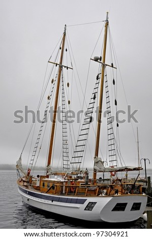 large sailboat anchored at the Pier during fog in Halifax Harbour, Nova Scotia Canada - stock photo