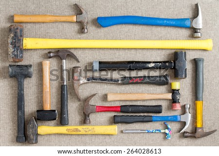 Large selection of different hammers and mallets arranged on a neutral beige background viewed from above in a DIY, renovation, maintenance,and construction concept - stock photo