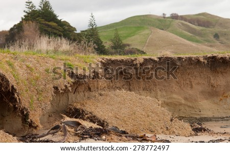large shard of turf falling onto beach after coastal erosion undermines land   - stock photo