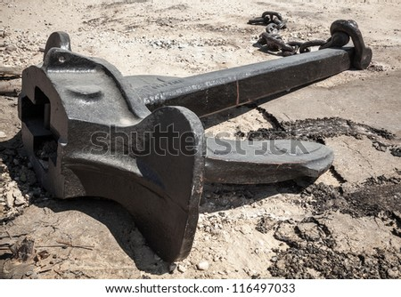Large ship's mooring anchor with broken chain on the ground - stock photo