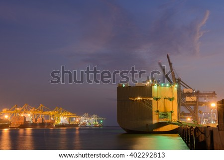 Large ship with operating crane at harbor night time - stock photo