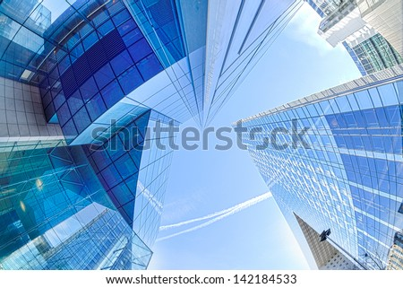 Large skyscrapers shot with a fisheye lens La Defense major business district near Paris, France . Abstract business background with office building skyscrapers  - stock photo