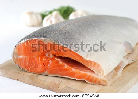 Large slab of tail portion of fresh Atlantic salmon on wooden chopping board - stock photo