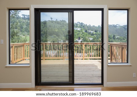 Large sliding doors open a view of beautiful wood balcony deck and nature - stock photo