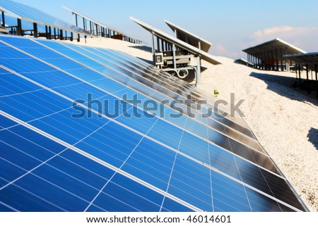 Large solar panel installation (selective focus on panel in foreground) - stock photo