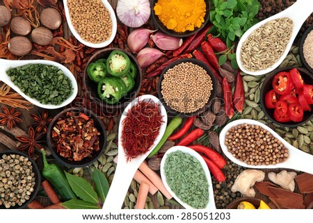 Large spice and herb collection in bowls and spoons forming an abstract background. - stock photo