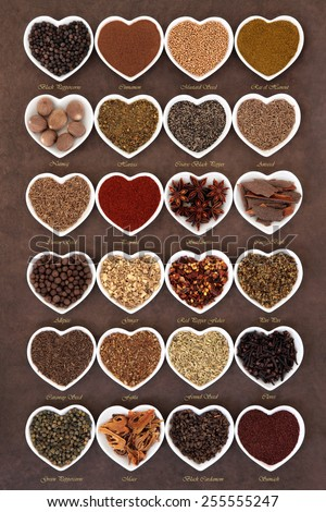 Large spice selection in heart shaped dishes over lokta paper background with titles. - stock photo