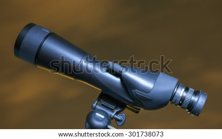 Large spotting scope with yellow and darkening clouds behind - stock photo