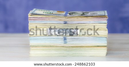 Large stack of paper currency located on wooden table and blue background. Soft light, reduced contrast. - stock photo
