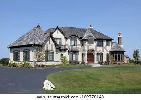 Large suburban white home with front turret - stock photo