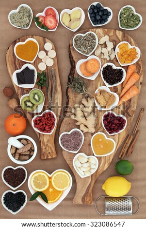 Large super food and medicinal herb selection for cold remedy with foods high in antioxidants on olive wood boards over white background. - stock photo