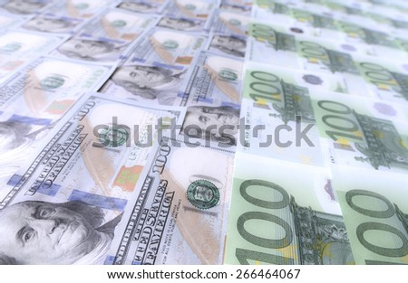 Large surface covered with US and European cash notes. High angle view of European and US hundred cash notes carefully spread out on the desk. Low contrast, soft light, perfect copy space. - stock photo