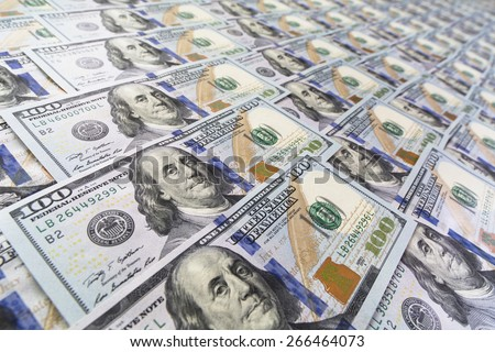 Large surface covered with US cash notes. High angle view of US hundred cash notes carefully spread out on the desk  - stock photo