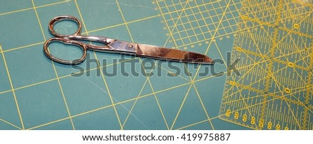 large tailor's scissors on the worktop with millimeter scale background of a company to create fashionable clothes - stock photo