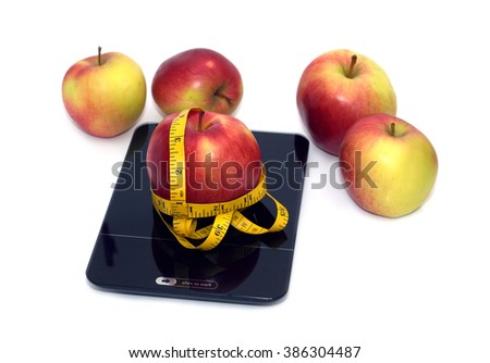 Large  tasty red and yellow ripe apples on kitchen scales and yellow measuring tape isolated on white background. Front view closeup - stock photo