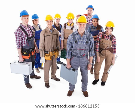 Large team of diverse artisans standing grouped together with their tools and hardhats lead by a handsome smiling foreman  high angle isolated on white - stock photo