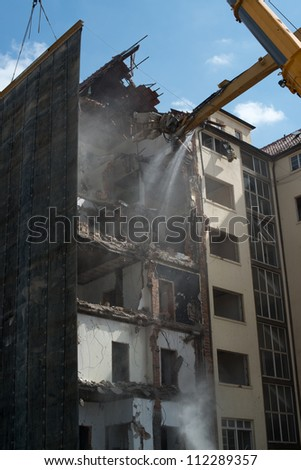Large tracked demolition excavator with concrete crunching demolition tool, ripping apart an old multistorey building whilst a heavy duty crane is applying a rubber mat to protect the surroundings - stock photo