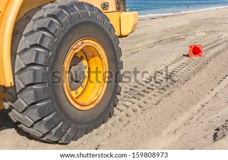 Large tractor tire leaves tread tracks in the sand on the beach. Close up of industrial vehicle heavy black tire. Fallen orange traffic cone, ocean, waves in background. - stock photo