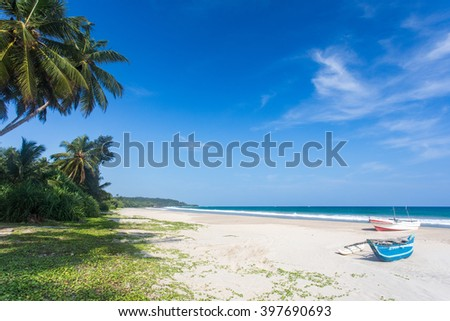 Large tropical beach with palm trees and white sand, blue sky and two boats on the shore in the sand. - stock photo
