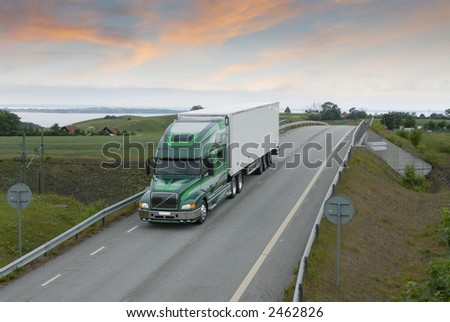 large truck, lorry driving on countryroad in early morning - stock photo