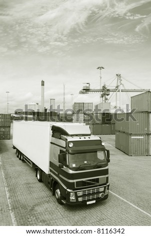 large truck standing in commercial port waiting for load. commercial container-port in background - stock photo