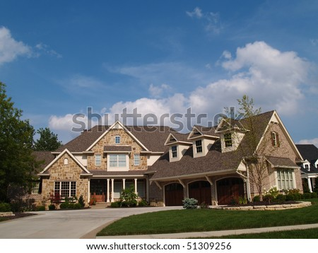 Large two story stone and brick residential home with garage in front containing plenty of copy space, - stock photo
