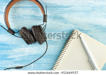 Large Vintage Leather headphones to play music lie next to a blank notebook with a ballpoint pen on blue wooden background. Mock up. Top view. Flat lay. - stock photo