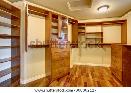 Large walk in closet with hardwood floor, also including many shelves and drawers. - stock photo