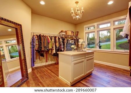Large walk in closet with hardwood floor and an island. - stock photo