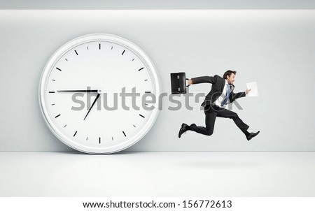 large wall clock and running businessman - stock photo