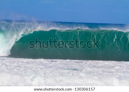 Large waves break off the north shore of oahu hawaii during a great time for surfers surfing. These waves have hollow barrells and are located at pipeline by sunset beach. - stock photo
