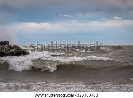 Large waves crashing against shoreline rocks on Lake Michigan in Milwaukee, Wisconsin in the morning with blue cloudy sky - stock photo
