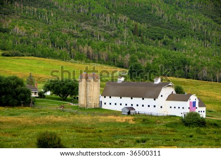 Large White Barn In A Beautiful Green Valley With An American Flag Displayed - stock photo