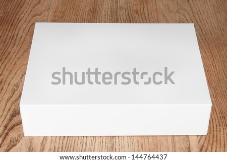 large white box on a wooden table - stock photo