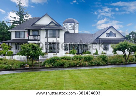 Large white house with blue trim and grass filled yard. - stock photo