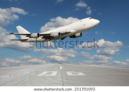 Large white plane without landing gear flies through over the runway - stock photo