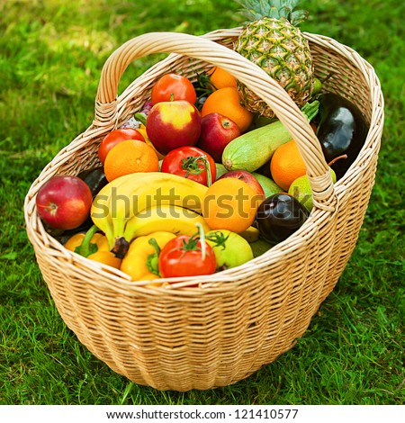 Large wicker basket with fruits and vegetables is on green grass. - stock photo