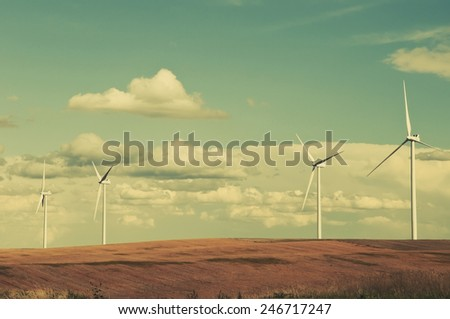Large wind turbines gathering electricity out of the wind in eastern Colorado, USA. Retro instagram look. - stock photo