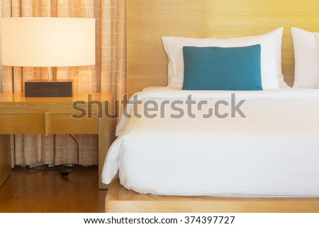 large wood bed with white duvet. - stock photo