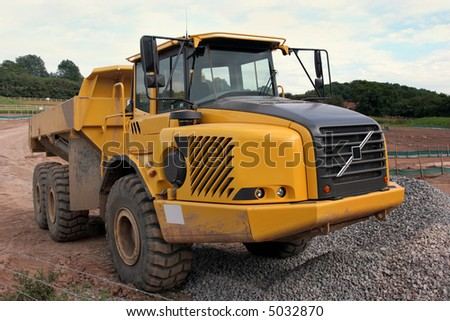 Large yellow dumper truck standing idle on a mud track on a building site, with a pile of gravel to the front. - stock photo