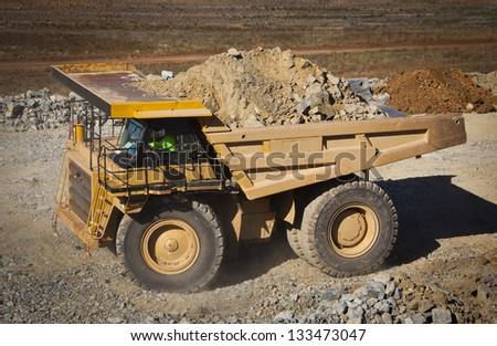 Large yellow truck used in modern Mine in Western Australia. Truck transports ore from the open cast mine. - stock photo