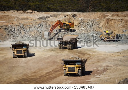 Large yellow trucks used in modern mine Western Australia. Digger fills empty trucks  which transport ore from the open cast mine. - stock photo